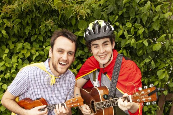 Two performers pose with a bicycle, playing guitar and ukelele