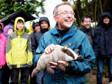 Nigel Fisher holds a plush toy badger, smiling while surrounded by people in brightly coloured rain coats