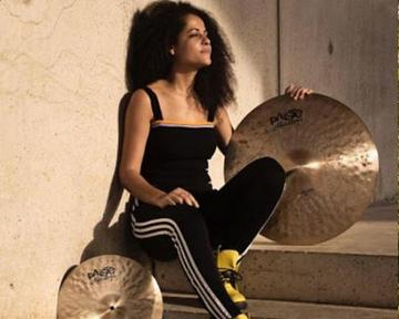 Jas sits on a step, holding a cymbal