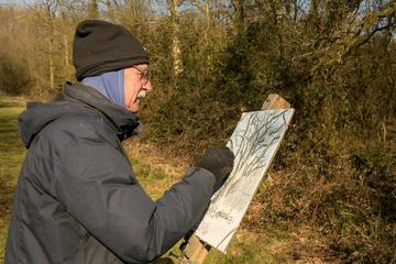 John Blandy is working on a small easel, sketching trees, wearing hat, gloves and scarf